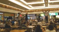 Jovens sobem nas mesas da praça de alimentação de um shopping para pregar