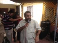 Pastor Dariosvaldo anuncia o Evangelho; Ao fundo, voluntário ora por folião