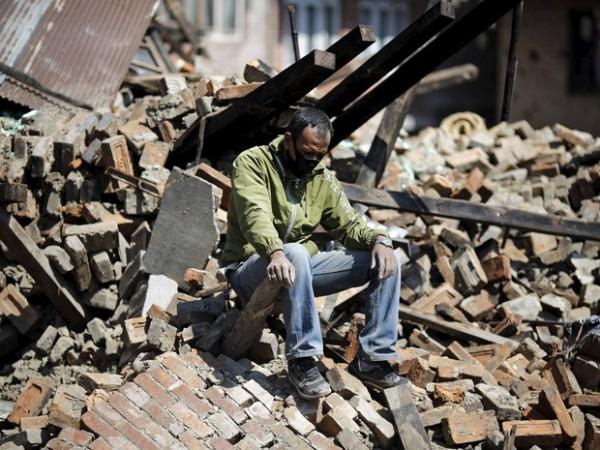 Homem desolado sobre escombros de edifício que desabou durante o terremoto